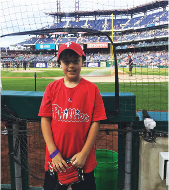 A young boy by the dugout at the Phillies baseball game